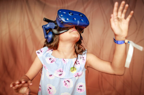 Young girl inside a virtual reality experience against orange background