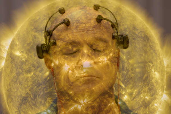 Man with probes on head and eyes closed with sun in backgound