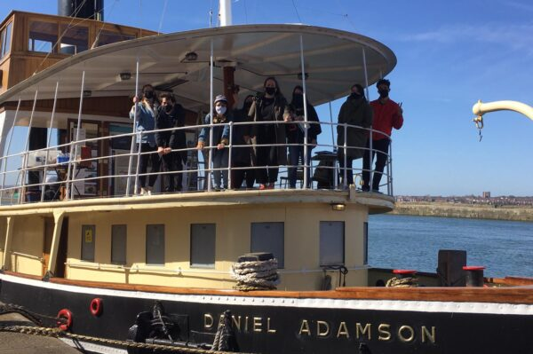People waving from the deck of a boat