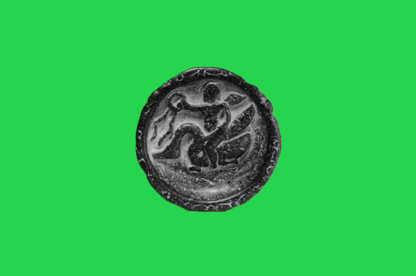 Old black coin on green background